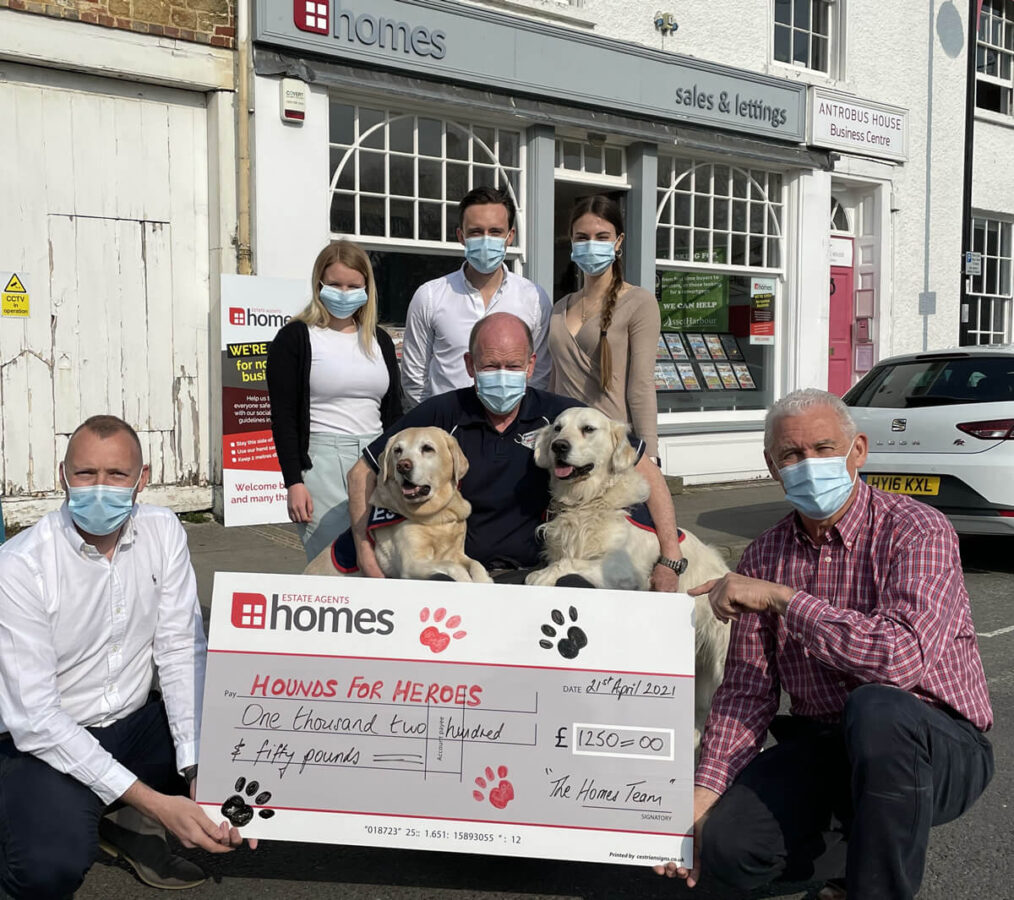 Pictured centre is Allen Parton, with his two remarkable assistance dogs EJ and Rookie, surrounded by members of the local Homes team